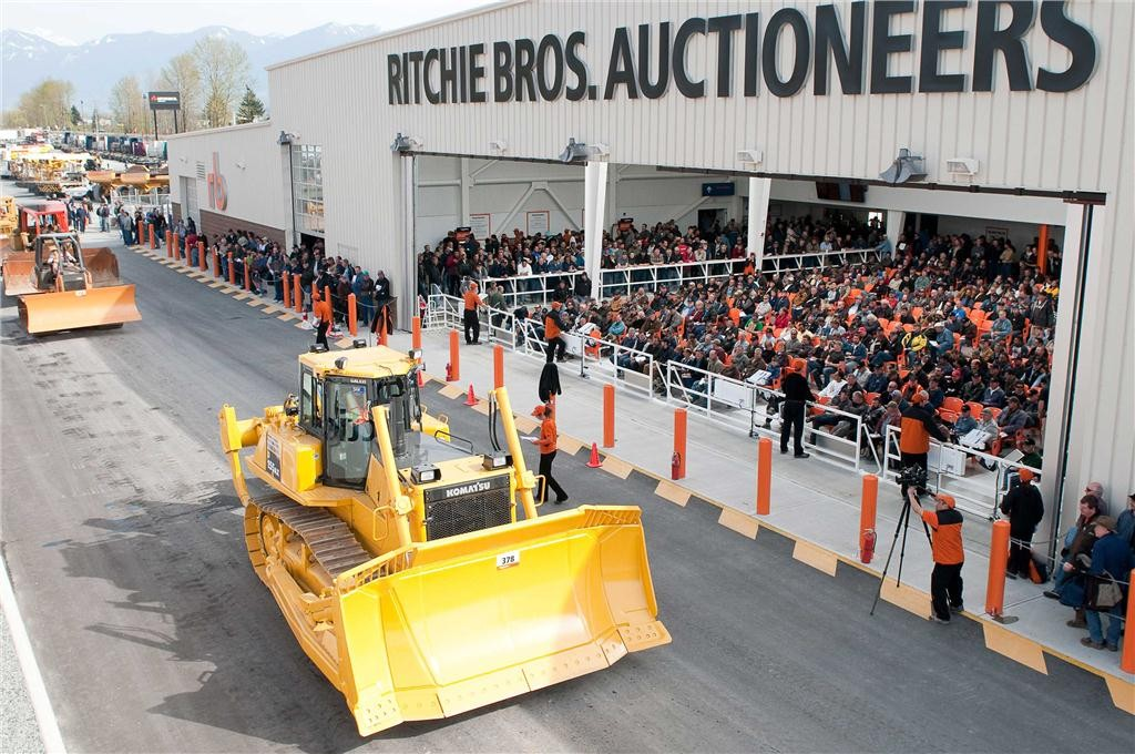 A crawler tractor crosses the ramp in front of a crowd of seated bidders in the auction theater in Chilliwack, B.C. in March 2010. Most mobile equipment is driven over a ramp in front of a crowd of bidders. (Photo courtesy of Ritchie Bros. Auctioneers)