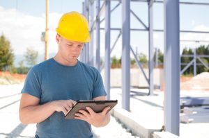 An architect reviewing plans at construction site on digital tablet