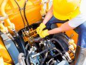 worker mechanic repairing construction vehicle