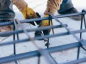 Construction worker hands securing steel bars with wire rod for cement reinforcement