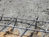 Wet concrete is poured into wire mesh