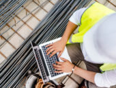 Construction engineer writing report on laptop at construction site