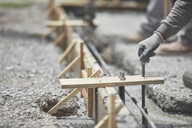Construction Worker placing Anchor Bolt into Wet Cement
