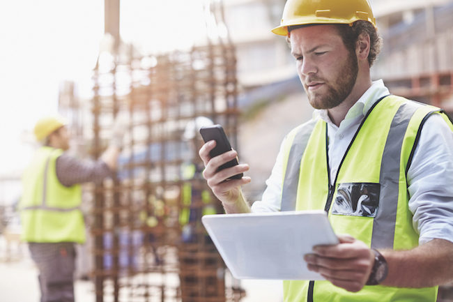 technology Construction worker digital tablet texting cell phone at construction site