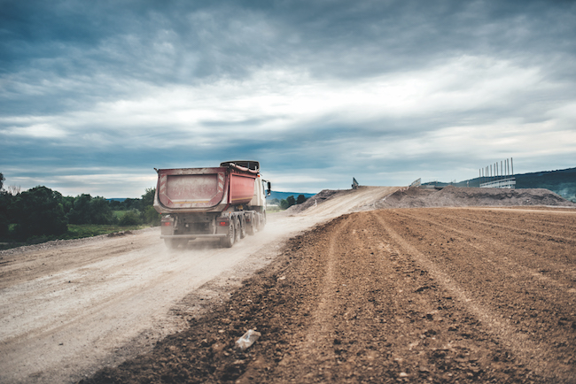 Industrial dumper trucks working on highway construction site, loading and unloading gravel and earth.