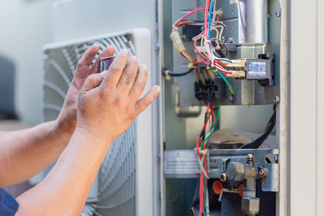 Selective focus of technician man hands using smartphone take a photo air conditioning system for attach in report