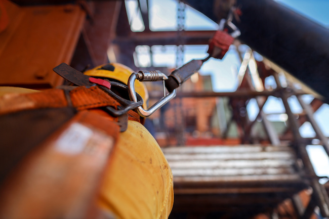 Side view of construction welder wearing safety helmet, fall arrest harness clipping retraceable device energy shock absorber lanyard on the back of his safety harness loop to preventing falling down