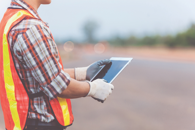 Asian engineer with hardhat using tablet inspecting and working at construction site