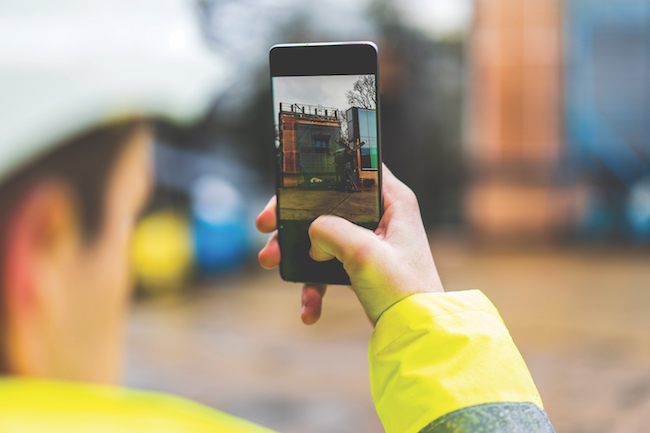 Architects holding a smartphone on construction site – young construction worker is using mobile phone on site – Construction worker with building plans and cellphone – Focus on mobile. warm filter