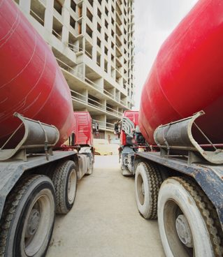 Between two concrete mixer standing near unfinished tall high-ri